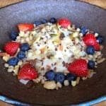 Porridge with seeds, nuts, fresh strawberries and blueberries in a bowl.