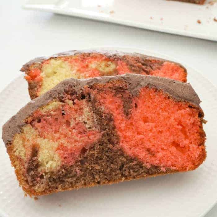 Two slices of marble cake with chocolate frosting, with swirls of vanilla, strawberry and chocolate cake texture.