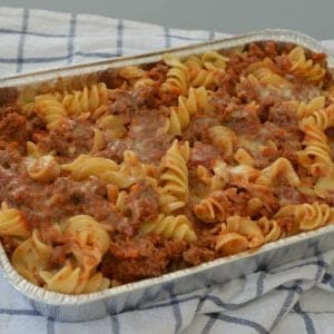 Spiral pasta and a tomato based meat sauce pasta bake in a rectangular baking dish resting on a tea towel