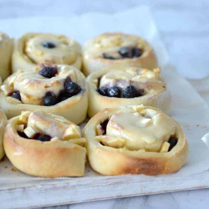 A bunch of baked scrolls with apple and blueberries rolled through and drizzled with white icing