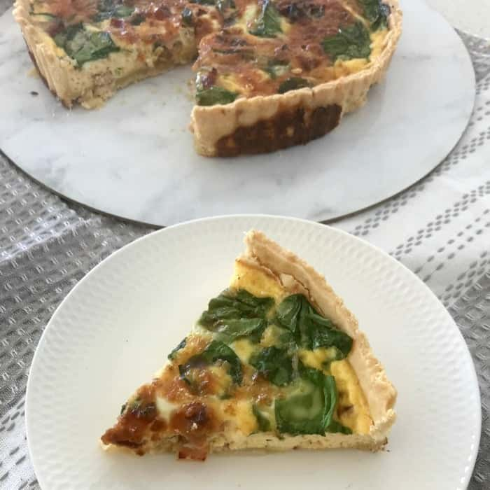 A serve of a pastry quiche with spinach, bacon and cheese on a plate with the rest of the quiche in the background