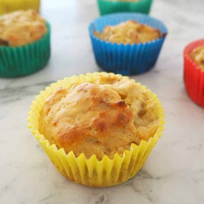 Apple and Cinnamon Muffins in green, blue, red and yellow muffin cases on a marble bench top.