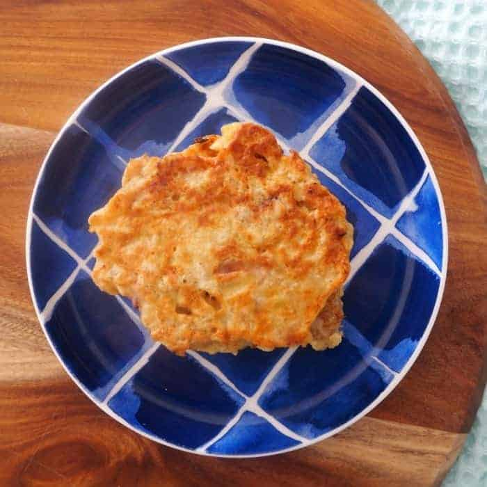 A golden pikelet made with apple and oats on a blue and white plate