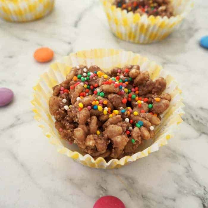 A cupcake case filled with Rice Bubble chocolate crackles, with colourful sprinkles on top
