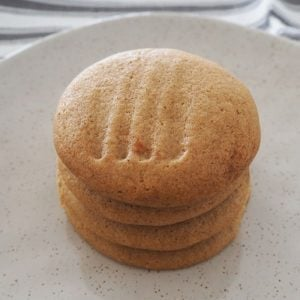 A white speckled plate with 4 ginger biscuits on top of one another.