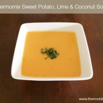 A square bowl of mustard coloured sweet potato soup, garnished with chopped coriander.