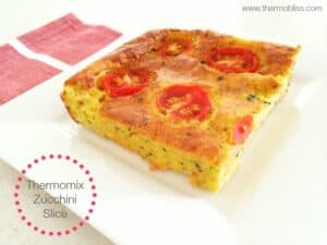 A square of zucchini slice with slices of tomato baked on the top.