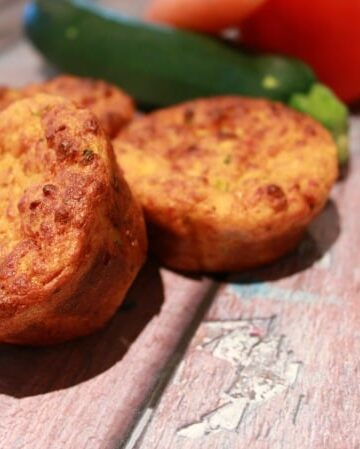 Golden baked savoury muffins on a wooden board.