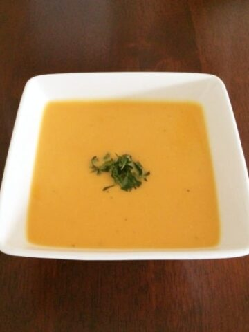 Sweet potato soup in a square white bowl, with chopped coriander on top.