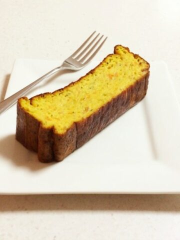 A square white plate with fork, and a serve of sweet potato and zucchini slice on it.