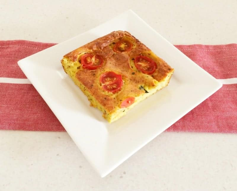 A serve of zucchini slice with sliced tomato on top, served on a white plate.