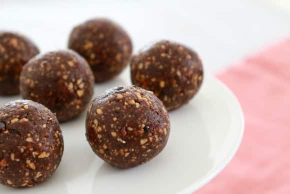 Small brown Bliss Balls with seeds visible, served on a plate