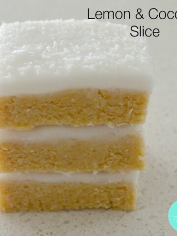 A stack of lemon and coconut slice with white icing and coconut sprinkled on top.