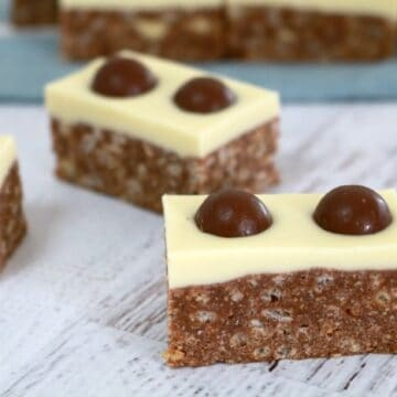 Malteser slice pieces with halved Malteser's pressed into the white chocolate layer on top.