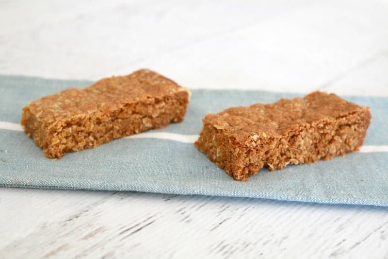 Two bars of a slice made with rolled oats, sitting on a blue tea towel.