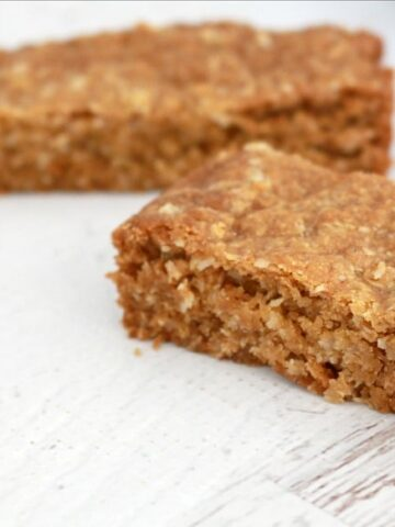 Two bars of a slice made with rolled oats on a bench.