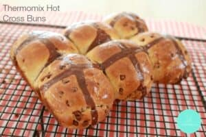 A batch of six Hot Cross Buns with a chocolate cross on top and chocolate chips inside.