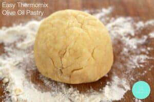 A ball of pastry dough made with olive oil on a floured board.