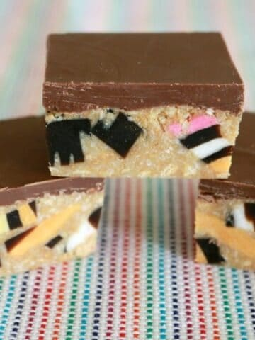 Squares of licorice all-sort slice topped with a layer of milk chocolate.