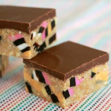 Squares of slice made with chunks of licorice all-sorts and a layer of milk chocolate on top.