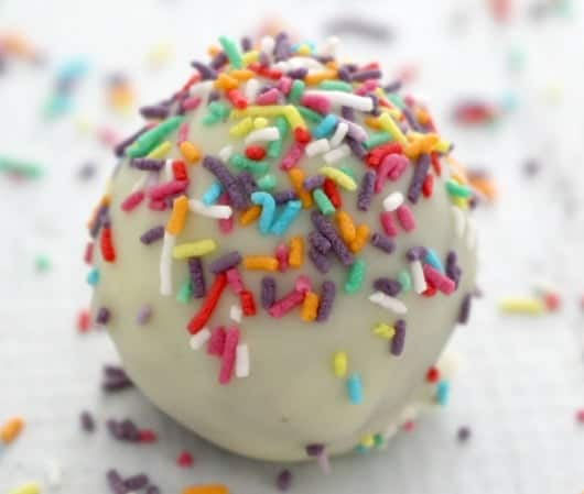 A close up of a Tim Tam ball coated in white chocolate and coloured sprinkles.