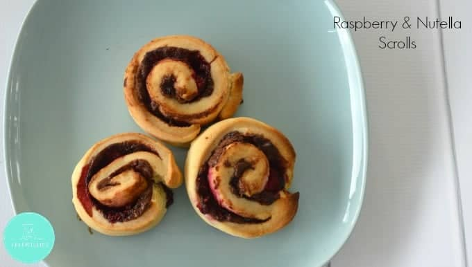 Raspberries and Nutella rolled through baked scrolls served on a plate.