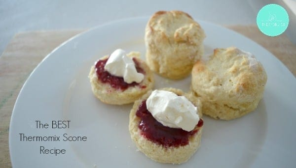 Plain scones on a plate with one scone cut in half and topped with jam and whipped cream.