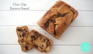 An overhead shot of a loaf made with banana and chocolate chips, with two slices cut to show chocolate chips throughout each slice.