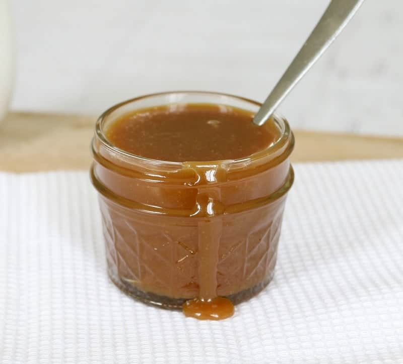Caramel sauce in a small glass jar with some sauce drizzling down the front of it.