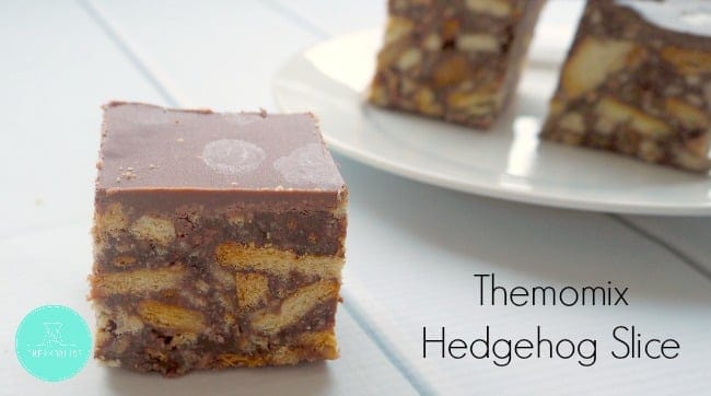 A layer of milk chocolate over a piece of chocolate hedgehog slice made with crushed biscuits.