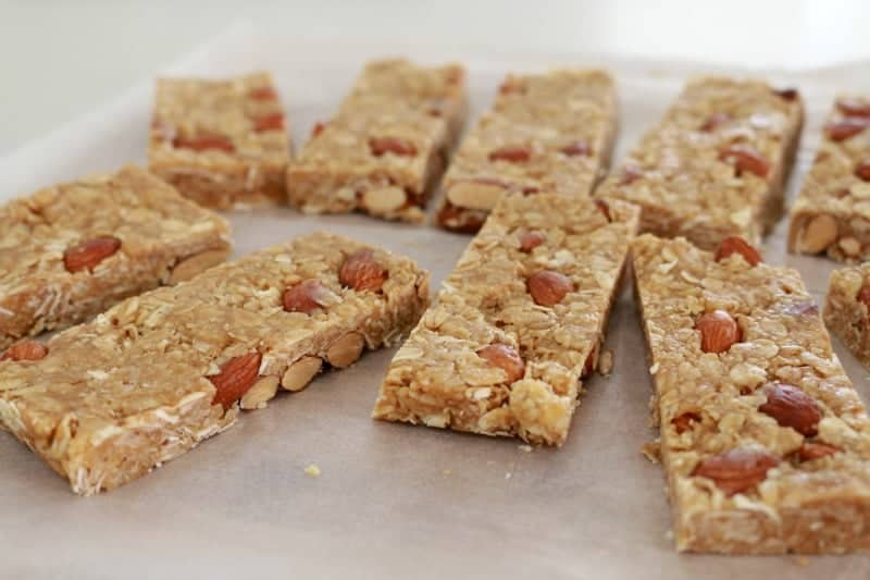 Bars of muesli slice, made with honey and nuts, on a bench.