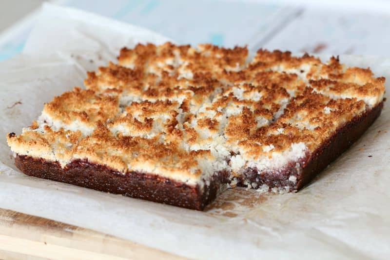 A slice with one square removed, with a chocolate base and a top layer of jam and toasted coconut.