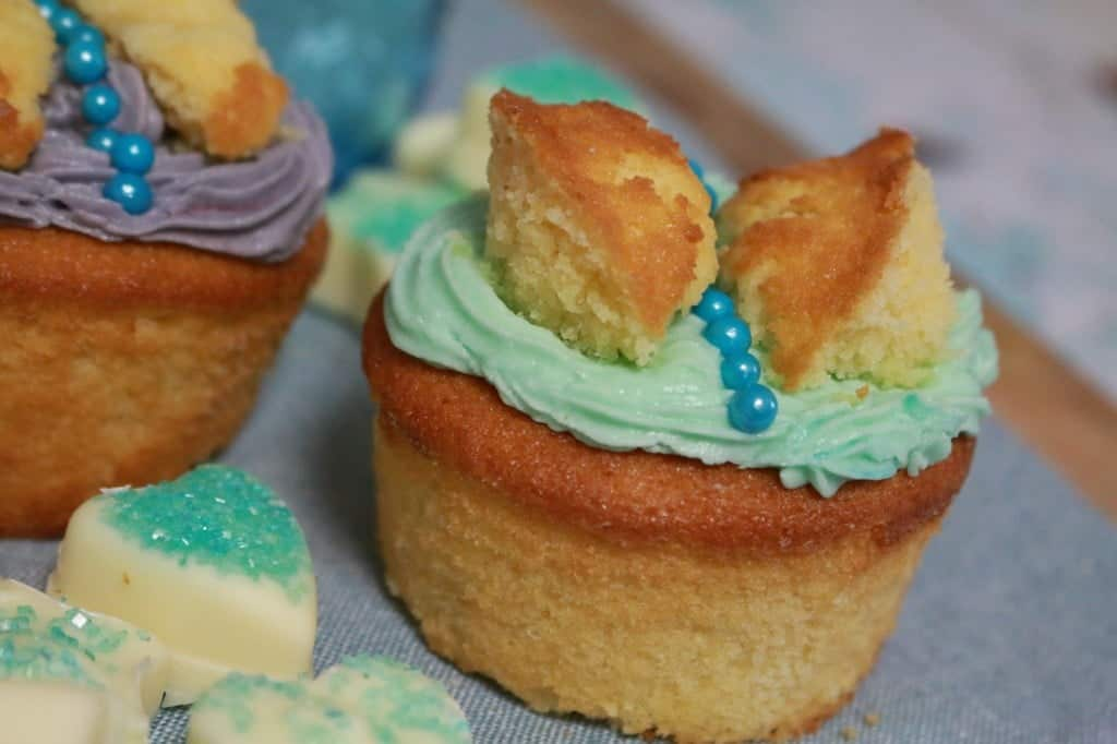 A close up of a butterfly cake made with a frosted cupcake and pieces of cake cut and placed on top to resemble wings.