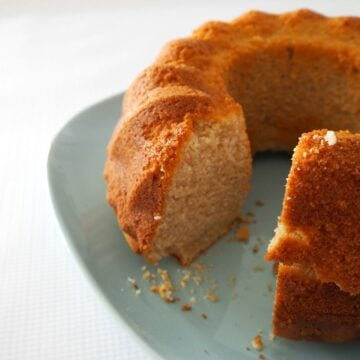 A cinnamon bundt cake served on a blue plate with one slice removed.