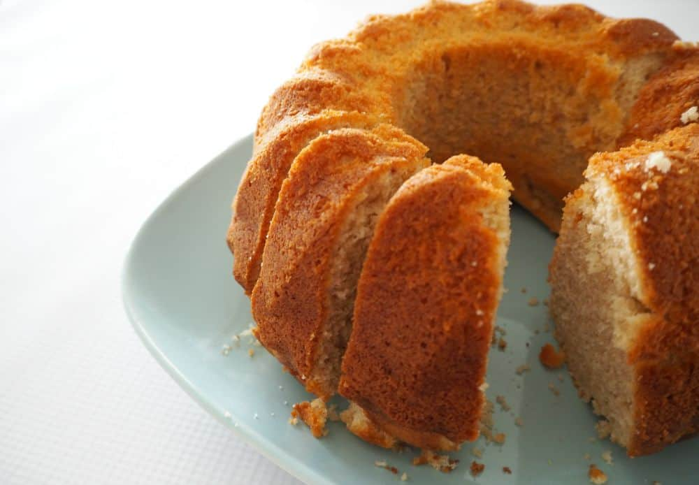 A cinnamon bundt cake on a plate with several slices cut