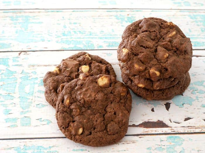 An overhead shot of four chocolate biscuits baked with milk and white chocolate chips inside.