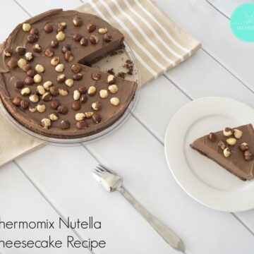 Toasted hazelnuts sprinkled over a chocolate Nutella cheesecake, with one serve removed and on a plate nearby.