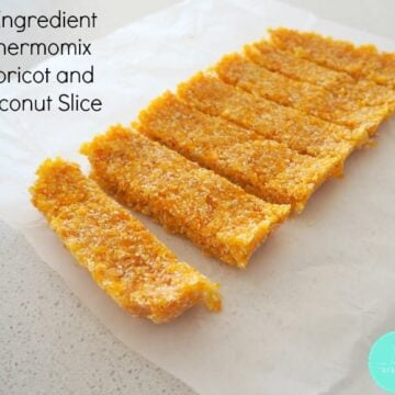 A slab of apricot and coconut slice cut into slices.