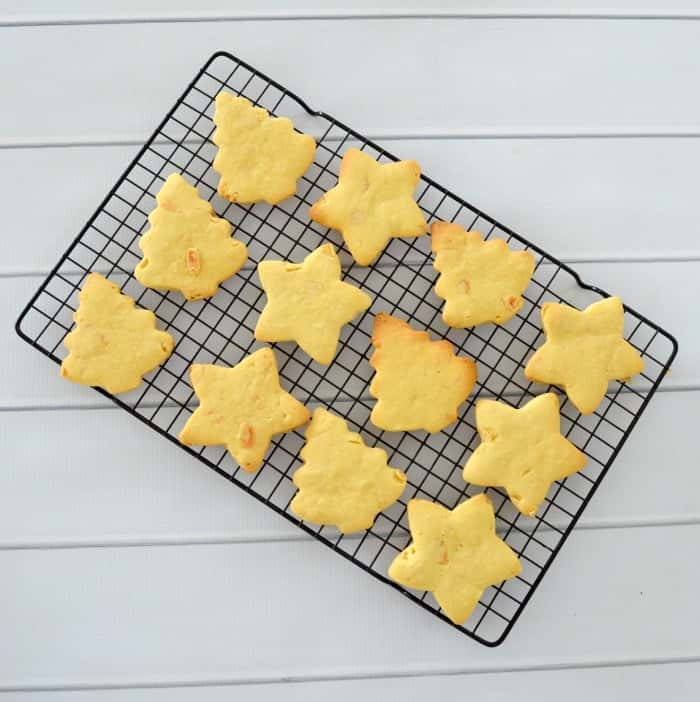 Almond shortbread cut into Christmas tree and star shapes on a wire tray.
