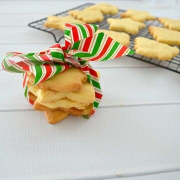 A stack of Christmas tree shaped shortbread tied with a red, white and green ribbon.