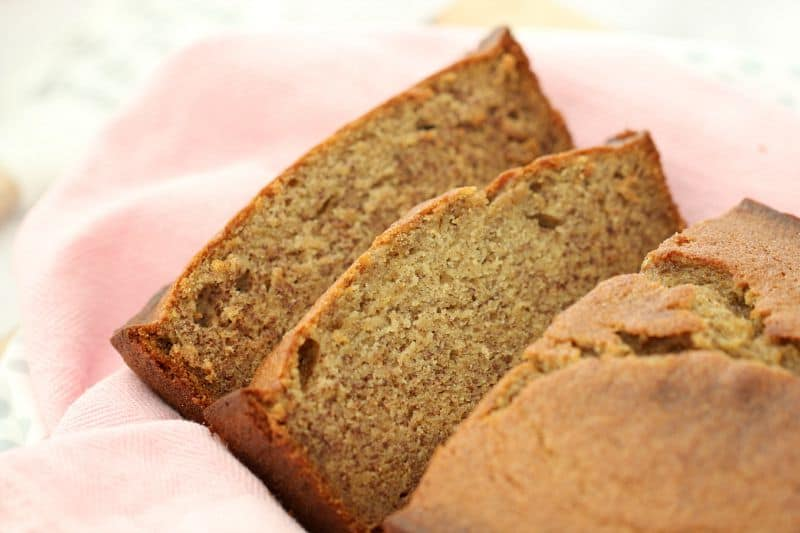2 slices of banana bread cut from a loaf sitting on a pink tea towel.