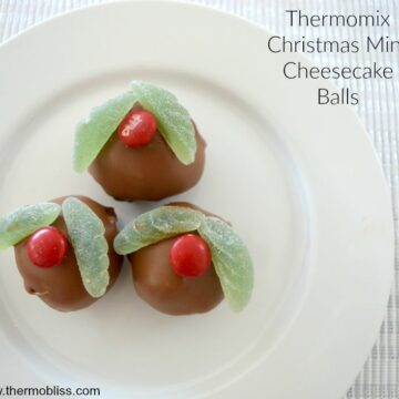 Three mini cheesecake balls coated in chocolate and decorated to resemble holly on a Christmas pudding.