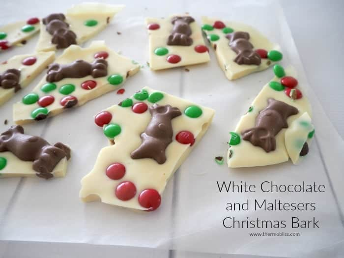 Chocolate reindeer and red and green M&M's on pieces of white chocolate bark.