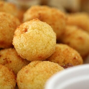 A close up of a pile of golden little arancini balls