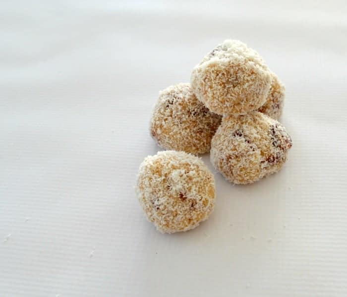 Five white chocolate and cherry balls rolled in coconut, in a pile.