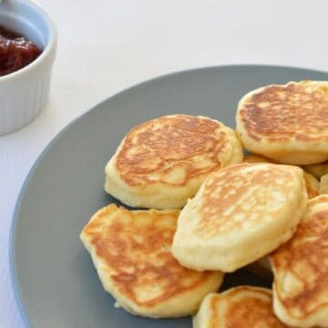 A plate with a pile of golden pikelets on it.
