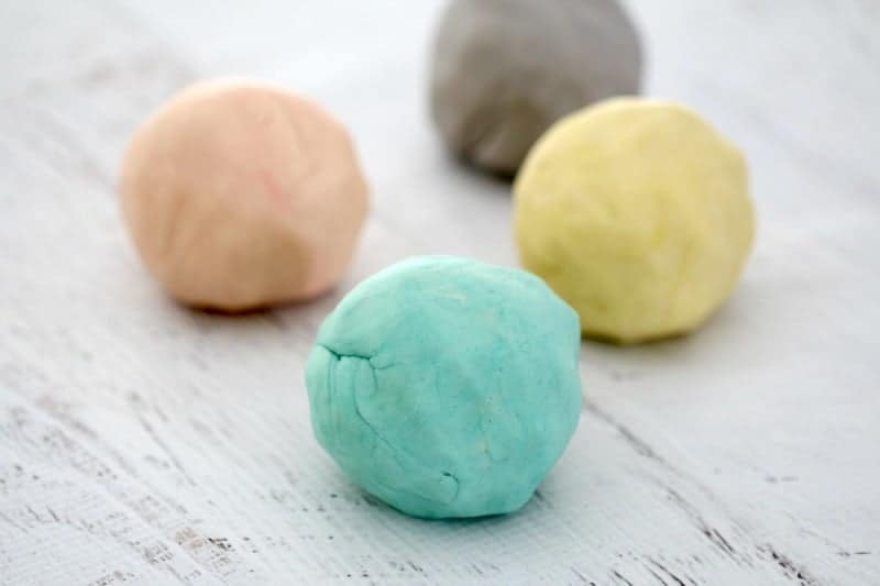 Balls of coloured playdough on a white board.