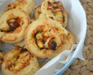 A basket filled with baked golden scrolls with spinach, feta and tomato rolled through them.