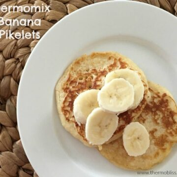 Banana pikelets on a plate with sliced banana on top.