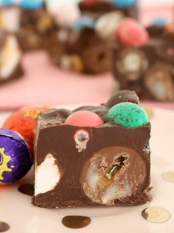 A close up of a piece of Rocky Road filled with creme eggs and mini coloured Easter eggs, with more Easter eggs beside.